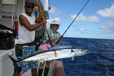 Both American Angler crewman Dave Ibrahim, and angler Karen Schantz are very happy about this nice wahoo caught during the PENN Fishing University 8-day trip.