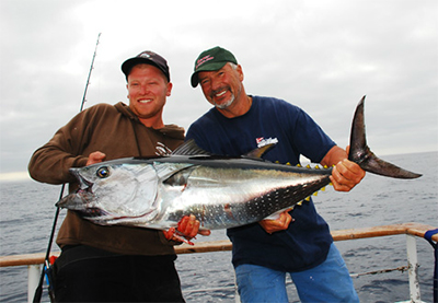 BRUTE BLUEFIN TUNA - Big bluefin tuna were around last summer and the Pacific Star got into many good stops. Pictured are (r) Captain Mike Bullard and first deck Matt Huffer with a 60 lb. bluefin tuna.