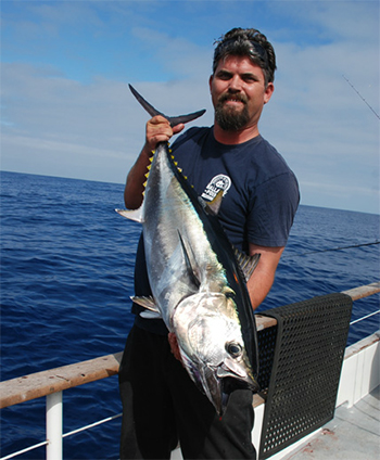 ONE QUALITY TUNA - Travis Tiglio of Oceanside holds up his bright bluefin tuna caught on live bait aboard the sportfisher Pacific Star.