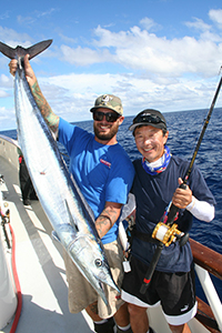 American Angler crewman Andrew Viola [L] does the heavy lifting for Dr.Chong Chang of Portland on another nice wahoo.